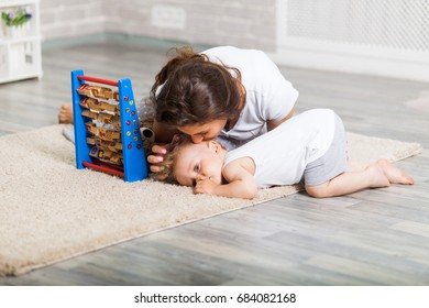 Mother with child playing educational toys in the room