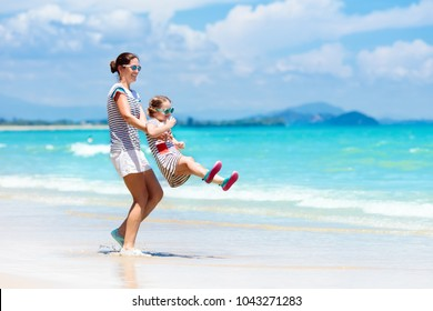 Mother and child playing at tropical beach. Family sea summer vacation. Mom and kid girl play and build sand castle. Ocean and water fun for parent and kids. Fit and healthy family at exotic beach.