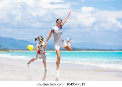 Mother and child playing at tropical beach. Family sea summer vacation. Mom and kid girl play and build sand castle. Ocean and water fun for parent and kids. Fit and healthy family at exotic beach