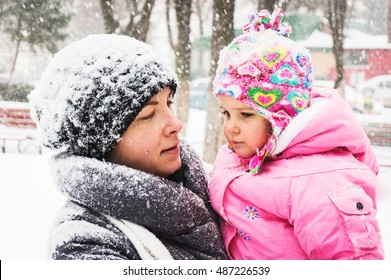 Mother and child portrait outdoors during heavy winter snowfall