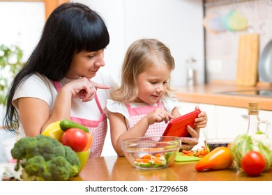 Mother and child preparing vegetables together at kitchen and looking at tablet for recipe