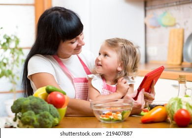 Mother and child preparing vegetables together at kitchen and looking at tablet for receipe