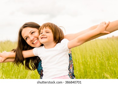 Mother and child pretend with hands they are together flying