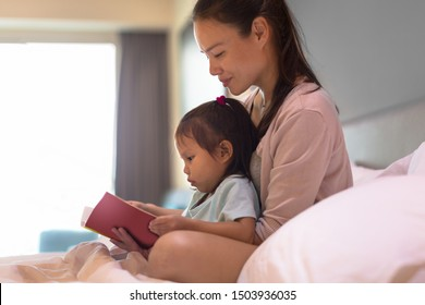 Mother and child reading a book in bed.