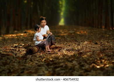 Mother and child reading book in forest,Asian women farmer wearing thai traditional dress sitting in rubber plantation,countryside thailand,Mother teaching daughter to read.