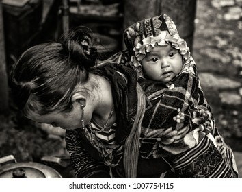 Mother and child, Sapa Vietnam april 2013 black and white photo, the mother was doing some cooking outside the house.