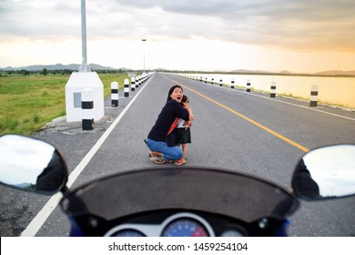 Mother and child are shocked that a motorcycle is about to crash on the road. Mother and child are hit by a motorcycle on the road. Concepts for accidents and safety. Front view motorcycle.
