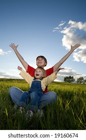 mother and child sit in field and hands up