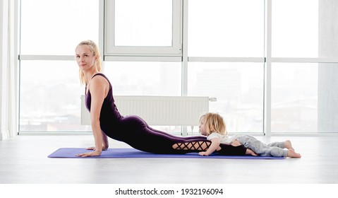 Mother and child son practicing partner yoga at home together. Sport family exercising