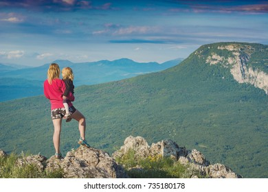 Mother with a child standing on cliff and enjoy beautiful mountain valley.