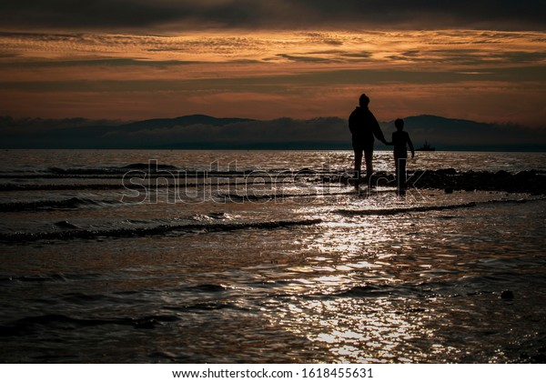 Mother and child standing together on the beach at sunset.