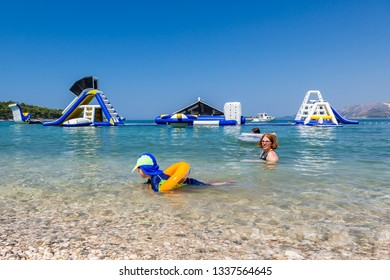 Mother and child swim and having fun in the water with inflatable slides in the background.