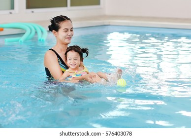 Mother and child swimming in the pool. Happy young woman teaching her daughter to swim. Little kid learning and exercising in the water.
