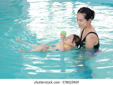 Mother and child swimming in the pool. Happy young woman teaching her daughter to swim