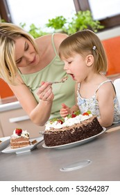 Mother and child tasting chocolate cake in modern kitchen