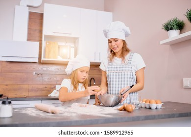mother and child together in kitchen, happy baking at home. little girl help to bake, to form dough, to make dough with use of chicken eggs and flour, wearing white caps and aprons. enjoy making food