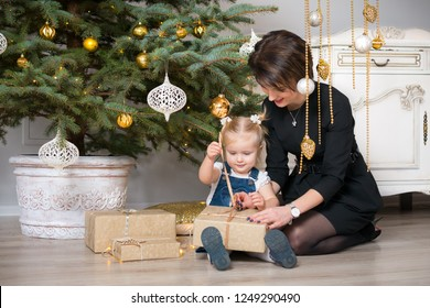 Mother and child unwrapping Christmas gifts while sitting on a floor next to a Christmas tree at home