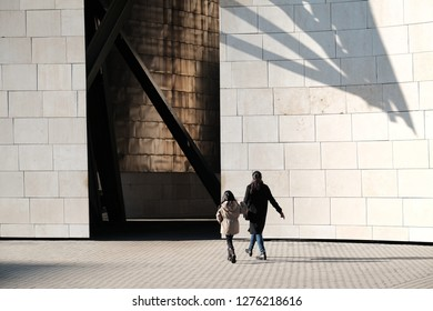 Mother and child walking to urban and futuristic museum