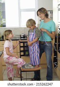 Mother and children (5-8) standing in kitchen, son (5-7) wearing striped apron, smiling, side view