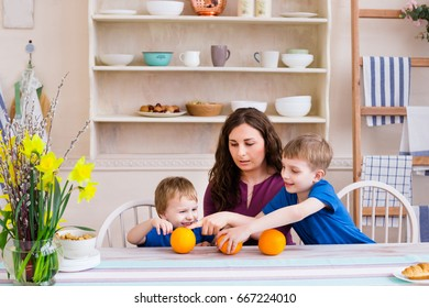 Mother and children care communication kitchen concept. Mother and kids at the table in the kitchen. Happy family concept. Children playing with oranges. Modern light kitchen.