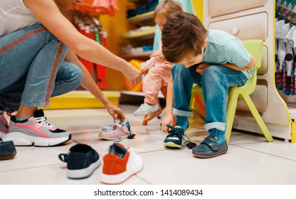 Mother with children choosing shoes in kids store