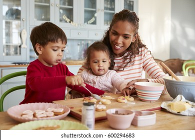 Mother And Children Decorating Cookies At Home Together