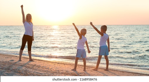 Mother and children do exercises on the beach, they meet the sunrise.Fitness, sport, yoga and healthy lifestyle concept.