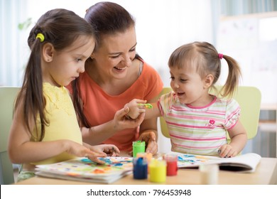 Mother and children draws with colored paints. Games with child affect early kids development.