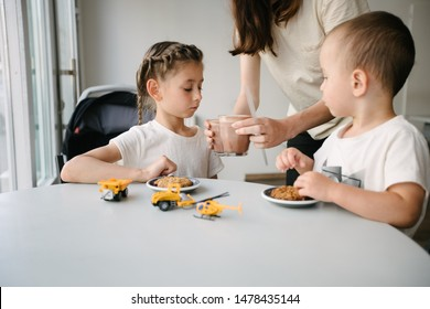 Mother with children drinking hot chocolate and latte at a local coffee shop. They are smiling and having fun. Motherhood concept