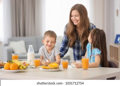 Mother with children having breakfast in kitchen