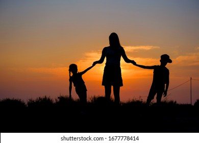 Mother and children hold hands in the background of the sunset.