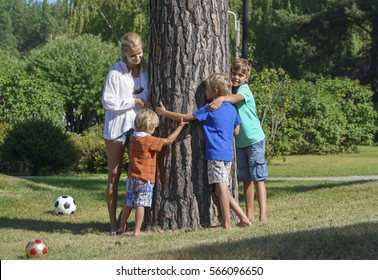 Mother and children hugging tree together in summer day
