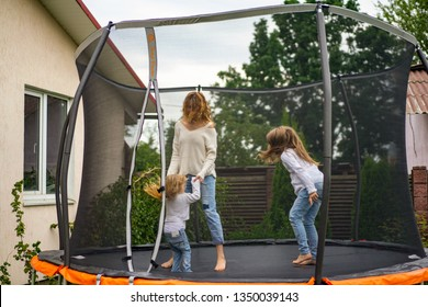 mother with children jumping on a trampoline. Summer day, trampoline in the yard, mother and daughter time together.