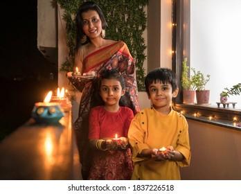 Mother with children lighting diyas in balcony