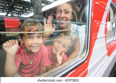 mother and children look from train window