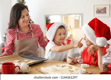 mother and children making christmas cookies together at home - Making Christmas Cookies