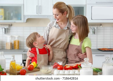 Mother and children making meal together in kitchen. Cooking classes concept