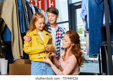 mother and children on shopping in stylish boutique during sale