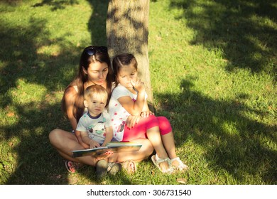 Mother with the children in the park reading a book