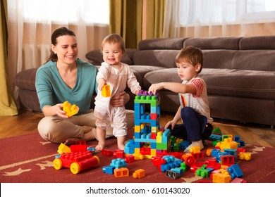 mother and children  playing with lots of colorful plastic blocks constructor indoor.  The happy family spends time together at home.