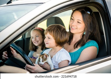 Mother and children pretend driving car sitting all on front seats