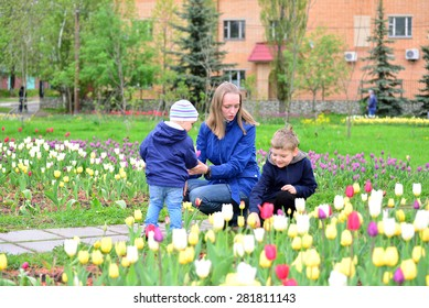 Mother And Children Relaxing  around the flower beds