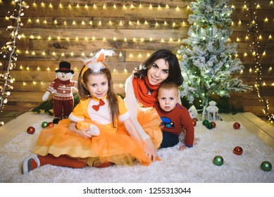 mother and children relaxing in christmas house