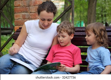 Mother with children sit on bench and read book