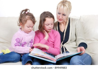 Mother and children sitting in living room reading book