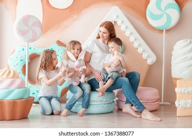 mother with children sitting on a large artificial sweets