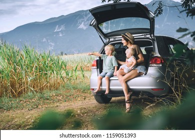 Mother and children sitting in an open car trunk and watching on nature and countryside. Family in road trip. Corn fields and mountains near Bled Lake, Slovenia, Europe. Travel, Lifestyle concept.