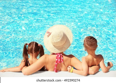 Mother with children in swimming pool at water park
