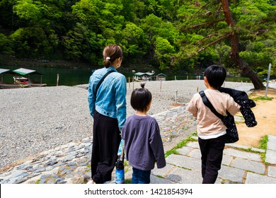 Mother and children walking along the Katsura River in Arashiyama, Kyoto, Japan