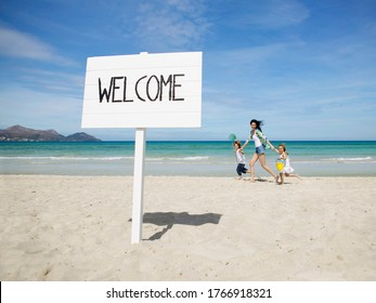 Mother and children walking behind Welcome sign at beach